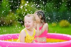 Adorable little girls playing in inflatable baby pool. Happy kids splashing in colorful garden play center on hot summer day. Royalty Free Stock Image