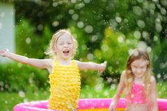 Adorable little girls playing in inflatable baby pool. Happy kids splashing in colorful garden play center on hot summer day. Summer activities for kids Royalty Free Stock Photos