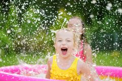 Adorable little girls playing in inflatable baby pool. Happy kids splashing in colorful garden play center on hot summer day. Summer activities for kids Royalty Free Stock Image