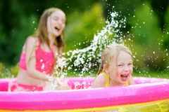 Adorable little girls playing in inflatable baby pool. Happy kids splashing in colorful garden play center on hot summer day. Royalty Free Stock Images