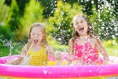 Adorable little girls playing in inflatable baby pool. Happy kids splashing in colorful garden play center on hot summer day. Summer activities for kids Stock Photography