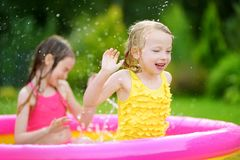Adorable little girls playing in inflatable baby pool. Happy kids splashing in colorful garden play center on hot summer day. Stock Image