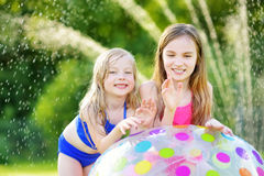 Adorable little girls playing with inflatable beach ball in a backyard on sunny summer day. Cute children having fun with water ou Royalty Free Stock Image
