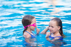 Adorable little girls playing in outdoor swimming Stock Photography