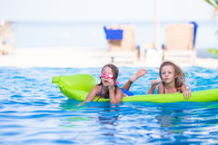 Adorable little girls playing in outdoor swimming. Pool Royalty Free Stock Photo