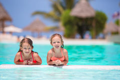 Adorable little girls playing in outdoor swimming pool Royalty Free Stock Photos