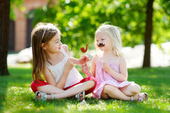 Adorable little girls playing with paper moustaches on a stick Royalty Free Stock Photography