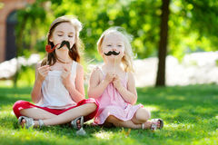 Adorable little girls playing with paper moustaches on a stick Stock Photos