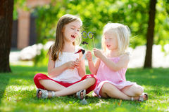 Adorable little girls playing with paper moustaches on a stick Stock Images