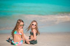 Adorable little girls playing with sand on the beach. Kid sitting in shallow water Stock Photography