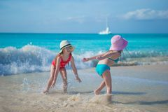 Adorable little girls playing in shallow water at Royalty Free Stock Photography