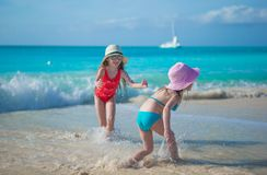 Adorable little girls playing in shallow water at Stock Photos
