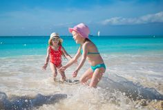 Adorable little girls playing in shallow water at Royalty Free Stock Image