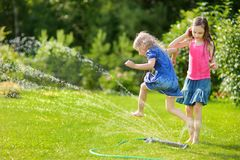 Adorable little girls playing with a sprinkler in a backyard on sunny summer day. Cute children having fun with water outdoors. Funny summer games for kids royalty free stock photos
