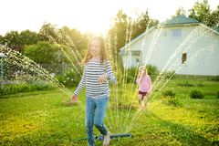 Adorable little girls playing with a sprinkler in a backyard on sunny summer day. Cute children having fun with water outdoors royalty free stock photo