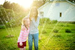 Adorable little girls playing with a sprinkler in a backyard on sunny summer day. Cute children having fun with water outdoors stock images