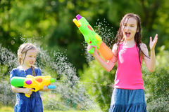 Adorable little girls playing with water guns on hot summer day. Cute children having fun with water outdoors. Royalty Free Stock Images