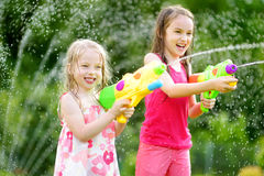 Adorable little girls playing with water guns on hot summer day. Cute children having fun with water outdoors. Stock Image