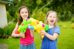 Adorable little girls playing with water guns on hot summer day. Cute children having fun with water outdoors. Royalty Free Stock Photos