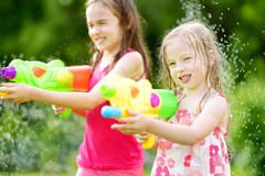 Adorable little girls playing with water guns on hot summer day. Cute children having fun with water outdoors. Royalty Free Stock Photography