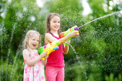 Adorable little girls playing with water guns on hot summer day. Cute children having fun with water outdoors. stock photo