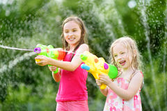 Adorable little girls playing with water guns on hot summer day. Cute children having fun with water outdoors. Royalty Free Stock Photo