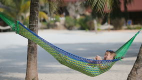 Adorable little girls relaxing in hammock on beach. Adorable little girls relaxing in hammock on the beach stock video