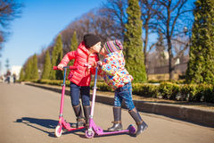 Adorable little girls ride scooters on a warm sunny spring day Royalty Free Stock Image