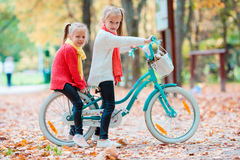 Adorable little girls riding a bike at beautiful autumn day outdoors Stock Images