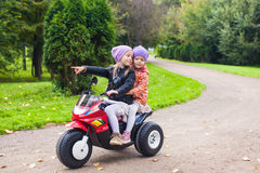 Adorable little girls riding on kid's bike in the Stock Photos