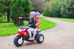 Adorable little girls riding on kid's motobike in Stock Image