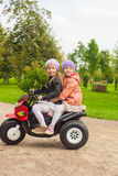 Adorable little girls riding on kid's motobike in Stock Images
