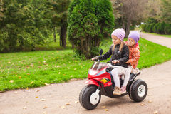 Adorable little girls riding on kid's motobike in Royalty Free Stock Images