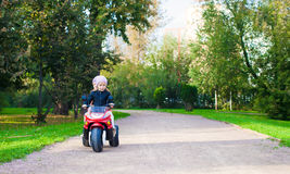 Adorable little girls riding on kid's motobike in Stock Photo