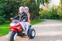 Adorable little girls riding on kid's motobike in Royalty Free Stock Photo