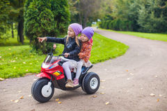 Adorable little girls riding on motobike in the Royalty Free Stock Photos