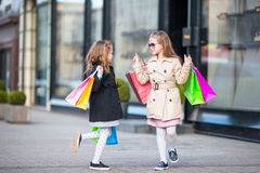 Adorable little girls on shopping. Portrait of kids with shopping bags. Royalty Free Stock Photography