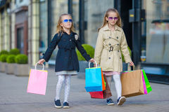 Adorable little girls on shopping. Portrait of kids with shopping bags. Stock Photos