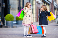 Adorable little girls on shopping. Portrait of kids with shopping bags. Stock Images