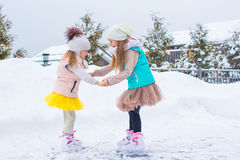 Adorable little girls skating on ice rink outdoors Stock Photo