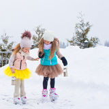 Adorable little girls skating on ice rink outdoors Royalty Free Stock Photos
