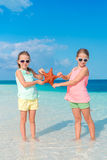 Adorable little girls with starfishes on white empty beach Royalty Free Stock Images