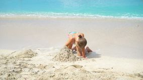 Adorable little girls during summer vacation on the beach. Adorable little girls during summer vacation on white beach. Cute kid playing with sand stock video
