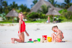 Adorable little girls during summer vacation. Kids playing with beach toys on the white beach Royalty Free Stock Image