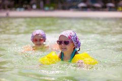 Adorable little girls swimming in clear sea Stock Photo