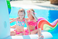 Adorable little girls at swimming pool having fun during summer vacation stock photography