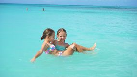 Happy little girls swimming in the sea during summer vacation. Adorable little girls swimming in the sea during beach vacation and having fun stock footage