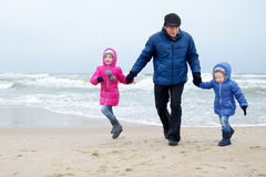 Adorable little girls and their grandpa playing by the ocean on winter day Stock Photos