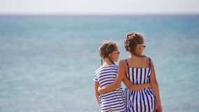 Adorable little girls together during beach vacation. Adorable little sisters at beach during summer vacation stock video