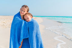 Adorable little girls together wrapped in towel at tropical beach. Cute little girls at beach covered with towel Royalty Free Stock Photography